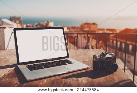 Modern laptop with empty white screen mock-up on the wooden table with retro film camera near; elegant netbook with empty screen template on table of cozy balcony in Lisbon city with cityscape behind