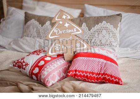 Christmas decoration consisting on wooden christmas tree and pillows with christmas pattern arranged on the bed