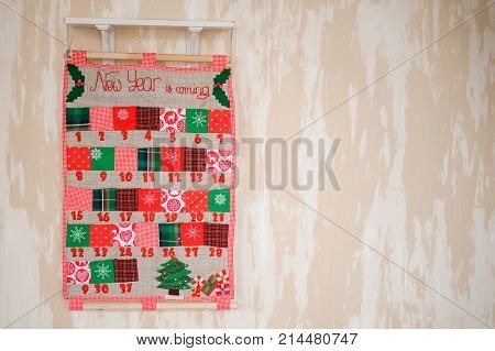Soft textile Christmas calendar decorated with textile christmas patterns and trees hanging on the wall