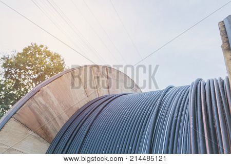 black wire electric cable with wooden coil of electric cable under the sky.