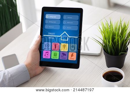 Man hand holding computer tablet with app smart home on screen in room