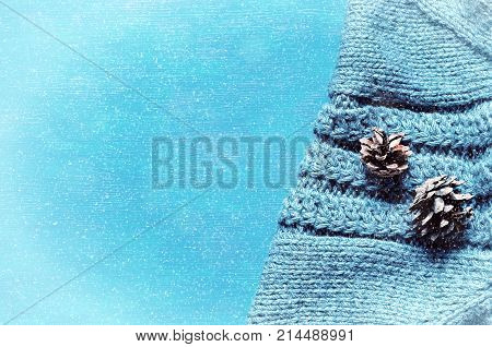 Winter background. Fir cones over gray knitted sweater with winter snowfall. Winter still life, free space. Colorful winter background, winter concept, flat lay top view. Winter composition