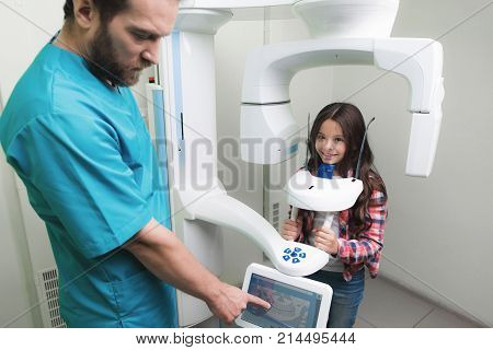 A male doctor makes an x-ray of the girl's jaw, which sits in a special X-ray machine. The girl is smiling. The doctor stands next to him and takes the indicators.
