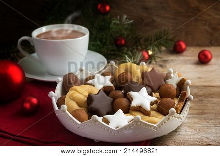 christmas cookies and a coffee cup with hot cocoa fir tree branches and red baubles on rustic wood for a cozy advent afternoon copy space selected soft focus narrow depth of field