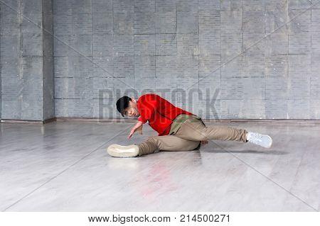 Stylish guy dancing break dance on floor. Handsome young man wearing red t-shirt and black cap posing in dance on the floor.