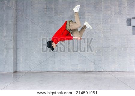 Rap dancer jumping on grey background. Portrait of a young male hip hop dancer jumping against grey background. Young rapper in high jump.