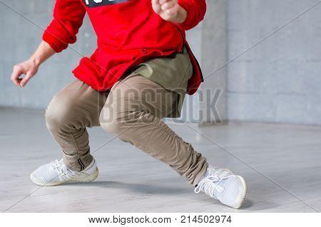 Stylish male hip-hop dancer in action. Trendy guy dancing break dance on grey background. Street style dancing.