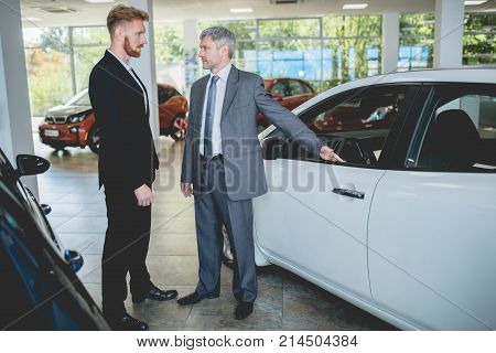 Young man at auto showroom talking with vehicle dealer. Man choosing electro car in car salon. poster