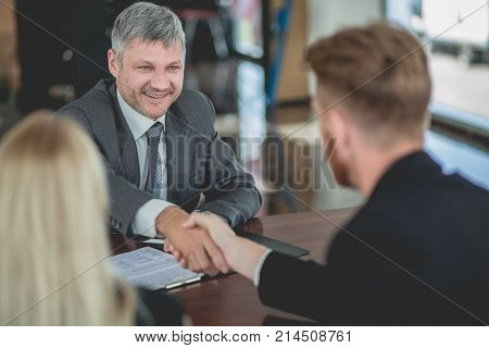 Auto dealer agent signing purchasing contract with a buyer, shaking hands. Buying new car concept, buyers and manager making deal.