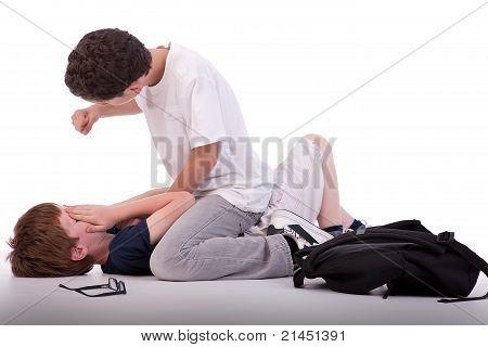 Niño llorando en el niño de suelo ser golpeado por un adolescente, aislado en blanco, Studio Shot