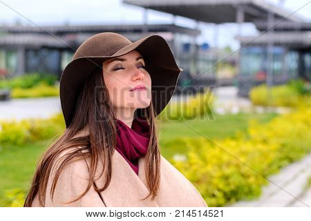 Young Attractive Woman In Sandy Coat And Brown Hat On, A Breath Of Fresh Air In A City Park On The W