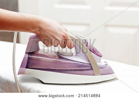 A woman ironing a hot electric iron on the ironing board.