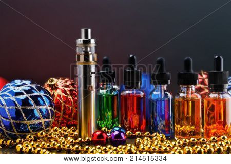 Electronic cigarette or vaping device, assorted vape liquids and christmas decorations on colored toned background