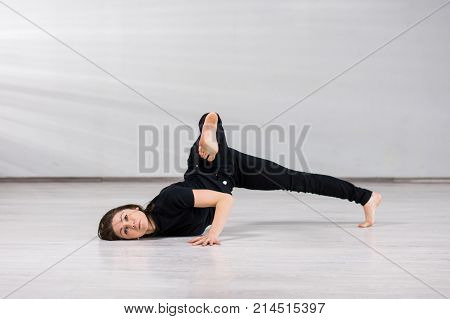 Girl dancer practicing dance element. Young beautiful dancer in gymnastic posing on studio background. Artistic and talented female dancer.