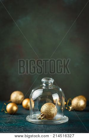 Golden Christmas ball under the glass cap on the background of other gold balls. Shallow depth of field.
