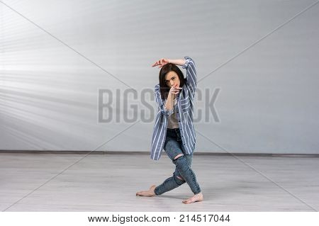 Young female dancer on studio background. Young pretty hip-hop dancer indicating with index finger forward. Talented and skillful young dancer.