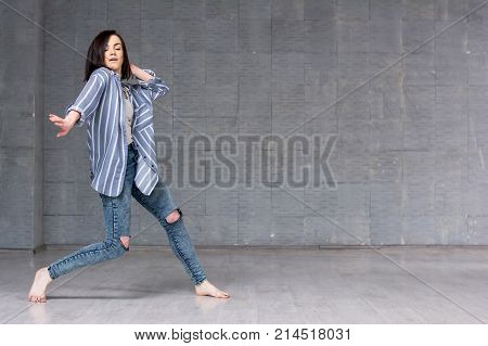 Young girl performing hip-hop dance. Young pretty woman dancing street dance on grey wall background.