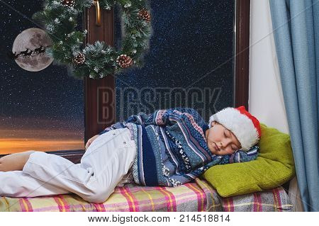 boy asleep on Christmas night .Boy in Santa hat sleeping on the windowsill . Merry Christmas