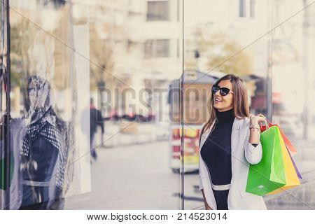 Smiling Woman Pointing At The Shop Window Before Entering Stor