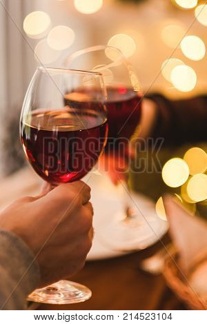 Hands cheering with glasses of wine. Dinner date for two. Romantic lights background. Love and food concept
