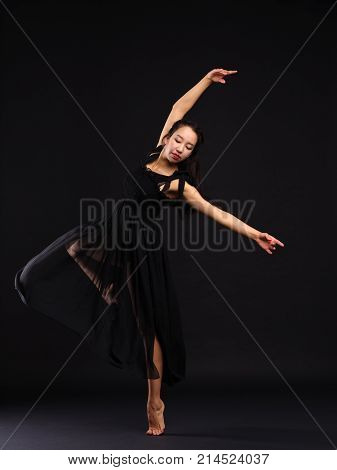 A young and talented girl dancer in a black dress is standing on one leg, bending her second leg in the knee and holding one arm up, and the other one is sideways. On a black background.
