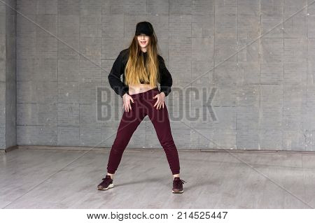 Casual girl dancer posing on grey background. Young caucasian modern style girl dancing contemporary dance in studio. School of modern dance.
