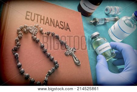 Rosary about a book of euthanasia, Doctor take one vial with pentobarbital used for the euthanasia and inyecion lethal, conceptual image