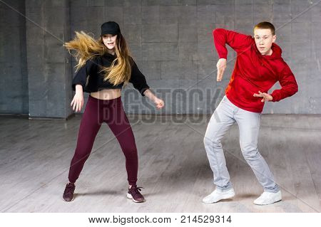 Attractive couple dancing hip-hop. Skillful modern style teenagers dancing contemporary dance on studio background.
