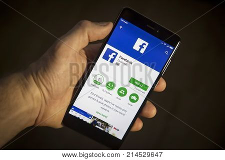 Berlin Germany - November 19 2017: Modern smartphone in hand with Facebook install menu on screen with application icon closeup. Facebook app in phone.