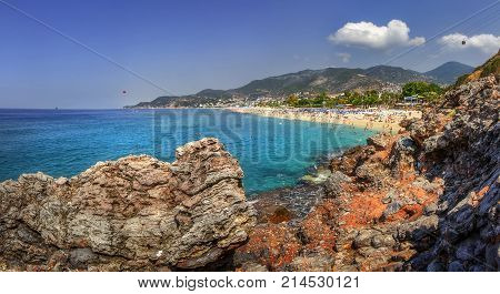 Seascape with rocky mountains and blue sea on sunny summer day. Panoramic landscape of Alanya beach Turkey. Summer vacation on tropical resort. Paradise lagoon bay with tourists on beach