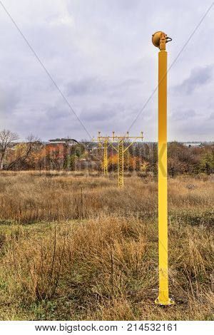 Yellow poles with landing lights for landing aircraft over houses