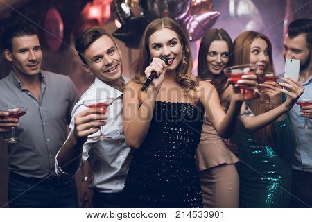 A woman in a black dress is singing songs with her friends at a karaoke club. Her friends have fun on the background. Everyone is very cheerful and they smile. They are in a trendy nightclub.
