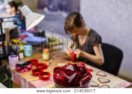 brown-haired woman manufacturing heart-shaped red purses under the lamp. purses are in focus. blurred background.