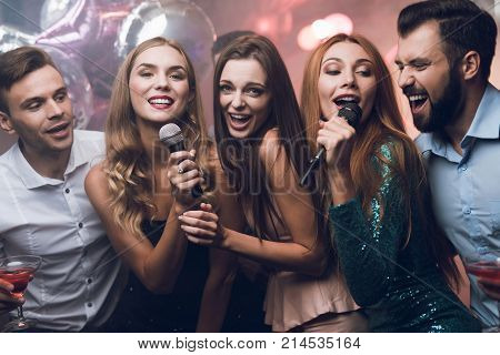 Three beautiful girls sing in a karaoke club. Behind them are men waiting for their turn. Young people have fun in a nightclub.