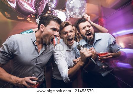 Three men sing at a karaoke club. Young people have fun in a nightclub. They are very cheerful and they smile. Against the backdrop of a beautiful, modern nightclub.