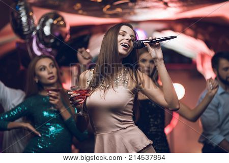 Young people have fun in a nightclub and sing in karaoke. In the foreground is a woman in a beige dress. She sings and her friends are dancing.