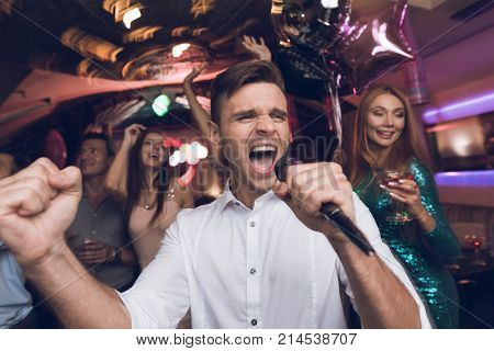 A man in a white shirt is singing in a nightclub. He has a microphone in his hands. Behind him, his friends are dancing and having fun. They are all having fun and they are smiling.