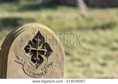 Ancestry and genealogy. Ancient gravestone inscribed with in memory of. Tracing a family tree using old cemetery headstones. Grave yard stone engraving. Blurred background with copy space. poster