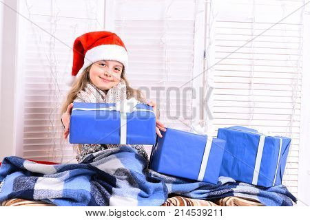 Santas Helper In Red Hat Covered With Blanket Holds Present