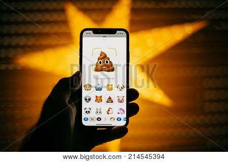 PARIS FRANCE - NOV 10 2017: poop 3d Animoji emoji generated by Face ID facial recognition system with different face emotion close-up of the new Apple iPhone X 10 Display - yellow star bokeh background
