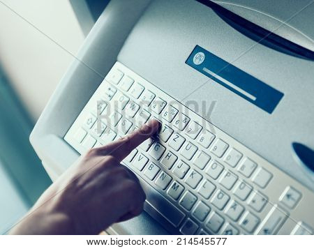 Modern filter over woman finger pressing the Y letter button on the metallic keyboard of ATM Automatic Teller Machine to retrieve withdrawal money or use other finance instrument