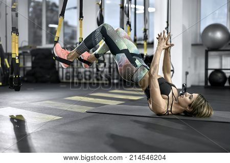 Cute girl is training with TRX straps in the gym. She leans on her shoulders on the mat while her feet are in the straps in the air. Woman wears colorful pants with black top and pink sneakers.