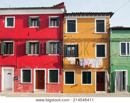 colourfull painted houses on a street in burano in venice in bright summer sunlight