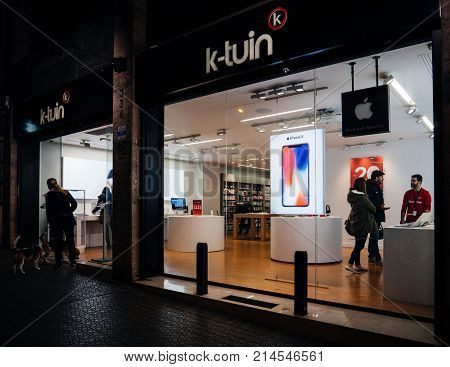 BARCELONA SPAIN - NOV 11 2017: People inside K-Tuin Authorized Apple Reseller buing for MacBook Laptop iPhone X and Apple Watch