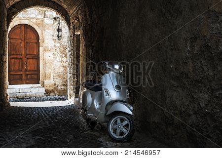 RHODES, GREECE - AUGUST 2017: Motorbike in dark arch of Rhodes town with old wooden door on a background. Rhodes island, Greece