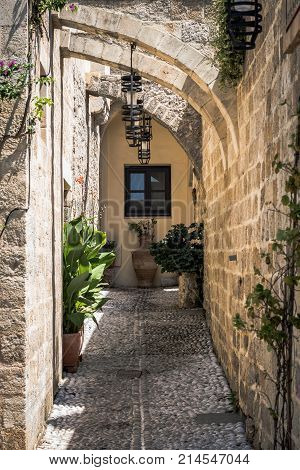 Small narrow street with ancient arches and walls in Rhodes town. Rhodes island., Greece