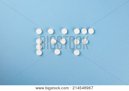 The word IVF, written on a blue background with white tablets. Selective focus