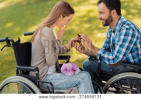 A man and a woman in wheelchairs met in the park. A man makes a woman a prepossess. She is delighted with such a surprise. They are in a beautiful green park.