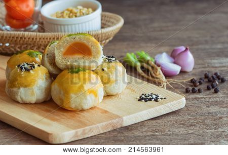 Chinese pastry or moon cake on wood cutting board with some ingredient on wooden table in side view with copy space. Homemade bakery concept. Delicious moon cake or chinese pastry. Chinese pastry and some ingredients. Chinese pastry background.