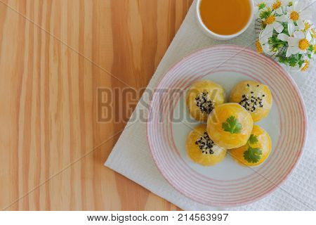 Chinese pastry or moon cake filled with mung bean paste and salted egg yolk on ceramic plate served with tea on wood table in top view flat lay with copy space. Homemade bakery concept. Chinese pastry background. Delicious homemade Chinese pastry.